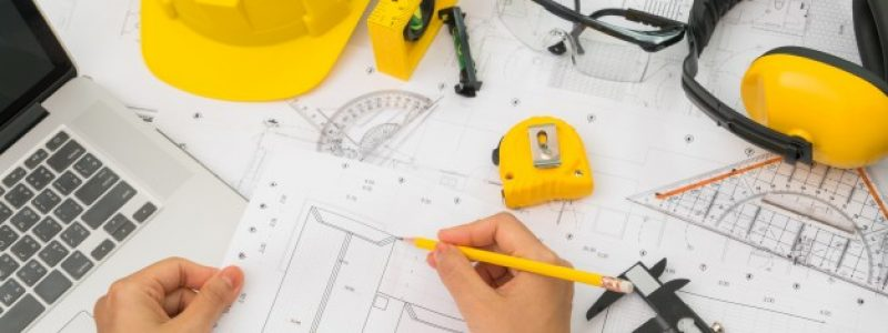 hand-construction-plans-with-yellow-helmet-drawing-tool_1232-2909